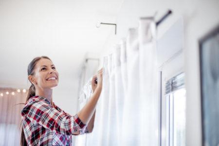 Frau hängt strahlend weiße Gardine auf