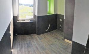 Der Boden erstrahlt in brauner Holzmaserung, die Wände sind schwarz marmoriert.