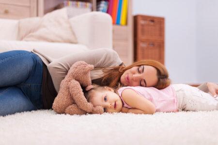 Frau und Kind auf Teppichboden