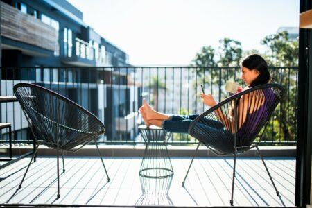 Junge Frau sitzt mit Kaffee und Smartphone auf dem Balkon ohne Sichtschutz.